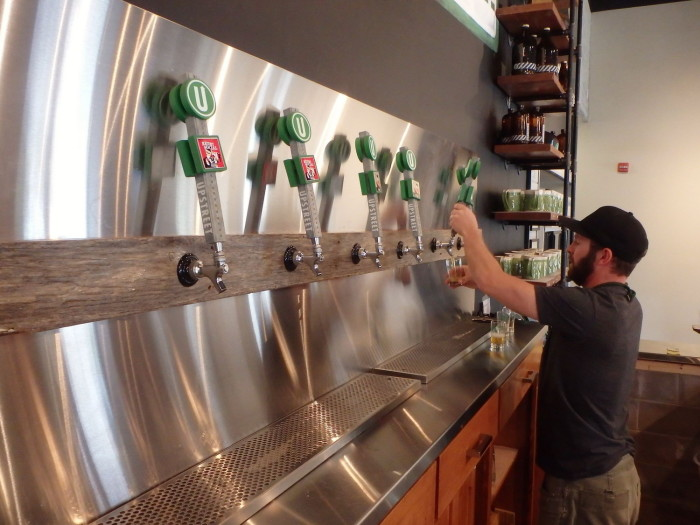 Joey pulls a cool ale at the Upstreet Taproom's bar.