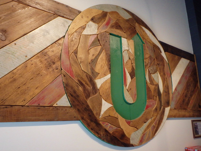 Handmade from salvaged wood, Upstreet's in-house artist designed a custom logo to grace the walls of the taproom.